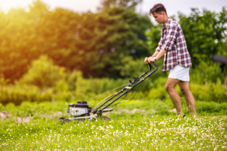 Handsone young man is mowing the lawn