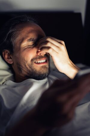 Bearded caucasian male is watching something on his tablet in bed at night. He is tired, cannot sleep and he clearly has a headache.