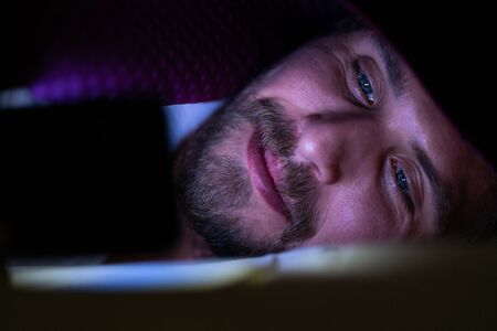 Bearded young man is lying in bed under his blanket. He cannot sleep and is watching something on his mobile phone.