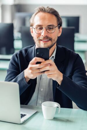 Jonge knappe man met een bril communiceert met zijn mobiele telefoon terwijl hij aan het werk is. Geluk en inhoud op het werk en altijd bereikbare begrippen.
