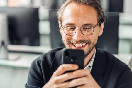 Jonge knappe man met een bril communiceert met zijn mobiele telefoon terwijl hij aan het werk is. Geluk en inhoud op het werk en altijd bereikbare begrippen. Stockfoto