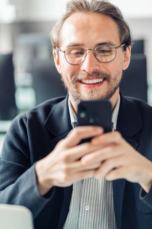 Young handsome man in glasses is interacting with his mobile phone while being at work. Happiness and content at work and being always reachable concepts.