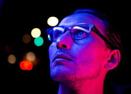 Modern red and blue light portrait of a young man in glasses. Streetlights visible in the background. Фото со стока