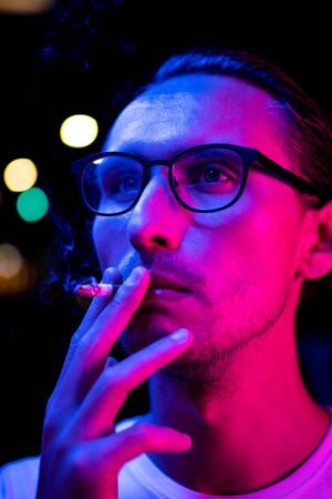 Vintage, red and blue portrait of a young man smoking a cigarette. Street lights visible in the background.