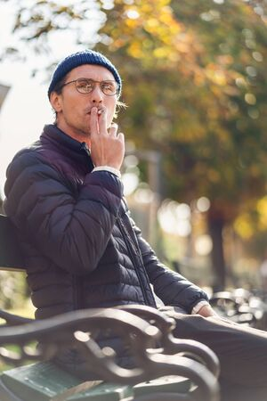 Young man in a cap smoking a cigarette on a bench during a nice autumn day. Banco de Imagens