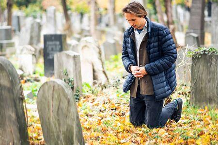 Joven de luto arrodillado frente a una tumba en un cementerio durante un triste día de otoño.