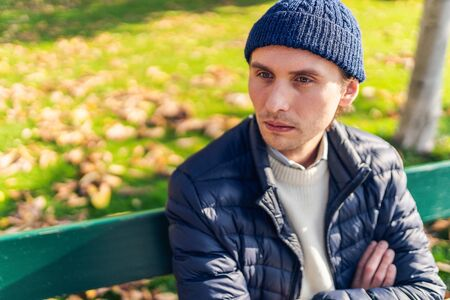 Rather serious young man in a cap on a bench during a sunny autumn day.
