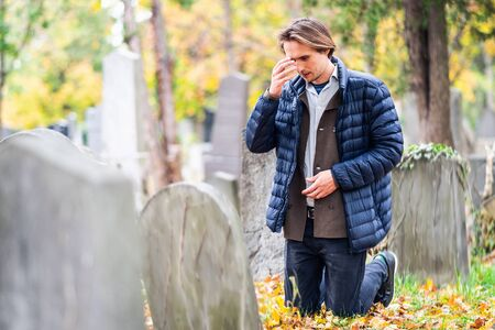 Mourning young man kneeling in front of a grave on a cemetery during a sad autumn day.