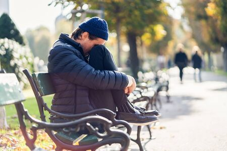 Young worried man is covering his face. He is sitting on a bench during sunny autumn day. Stock fotó - 133902895