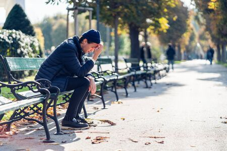 Young worried man is covering his face. He is sitting on a bench during sunny autumn day. 版權商用圖片