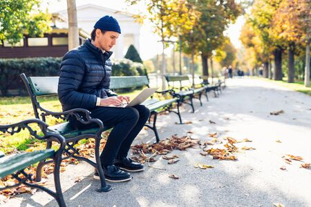 Young man in a cap is sitting on a bench during a nice autumn day. He is using his portable computer. Banco de Imagens