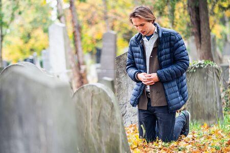 Trauernder junger Mann, der an einem traurigen Herbsttag vor einem Grab auf einem Friedhof kniet.