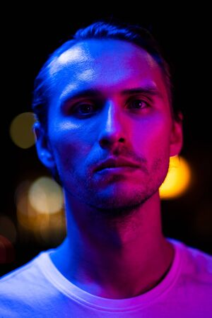 Modern red and blue light portrait of a young man. Streetlights visible in the background.