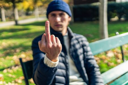 Young man showing fuck off gesture while sitting on a bench during a sunny autumn day.
