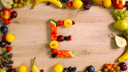 generates: Fruits made letter E. Alphabet on a table. Summer harvest generates letters.