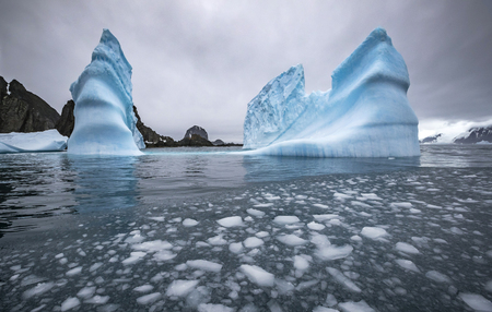 Landscape of icebergs and rocks in the sea. Pieces of ice float in the water. Andreev.