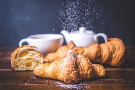 Sugar powder pours on the croissant. Archivio Fotografico