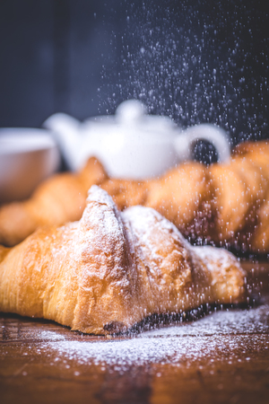 Sugar powder pours beautifully on the croissant. Archivio Fotografico