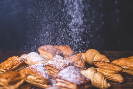 Sugar powder is poured onto buns from puff pastry.