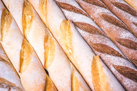 Wheat and rye baguettes lie side by side.