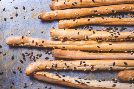 A close-up of bread sticks with seeds on an iron surface.