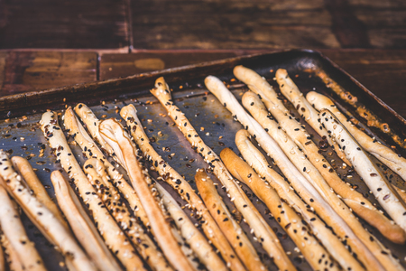 Bread sticks and a baking tray are strewn with seeds.