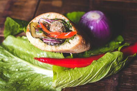 The sandwich lies on the salad sheet.