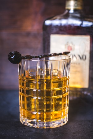 A crystal glass with alcohol on the background of a bottle and a smoke.