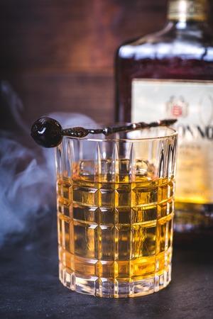 Whiskey or bourbon is poured into a glass. Фото со стока