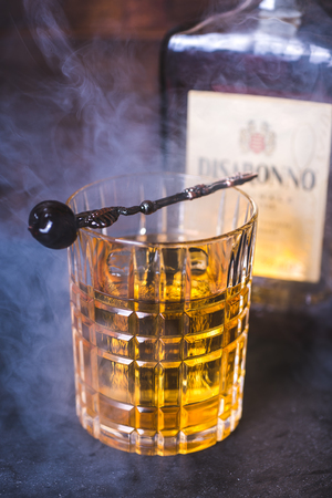A glass with an alcoholic beverage in the smoke. Фото со стока