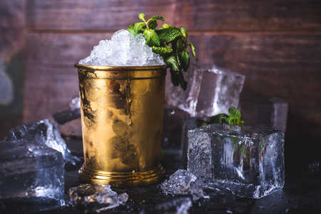 A container with ice stands among ice cubes and mint. A small iron bucket stands on a table with ice. Ice cubes lie in the background. Archivio Fotografico
