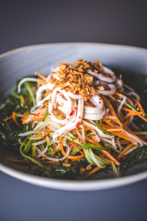 Close-up of a salad of Asian cuisine with carrots. Salad from pickled vegetables and seafood. A light deep dish stands on a blue surface.