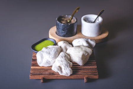 White crispy pies on a wooden stand. A container with a green sauce stands side by side on the stand. Marble glasses with spices in the background.