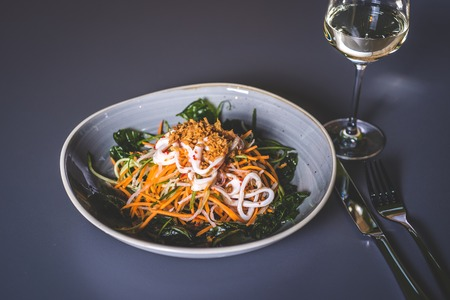 Salad with sea kale and seafood in a ceramic plate. The knife and fork lie next to the plate. Fougeres with white wine stands on the surface.