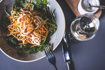 Top view of a salad of Asian cuisine and a glass of wine. A white marble glass is behind the dish. A fork lies on the edge of a plate with a salad. Fougeres with white wine stands on the surface. Фото со стока