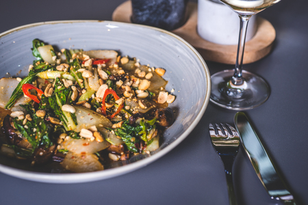 The dish is sprinkled with peanuts from above. The leg of the glass stands near the plate. The knife and fork lie next to the plate.