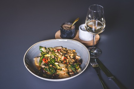Salad with meat and peanuts with sauce. The knife and fork lie next to the plate. Fougeres with white wine stands on the surface. Marble glasses with spices in the background. Фото со стока