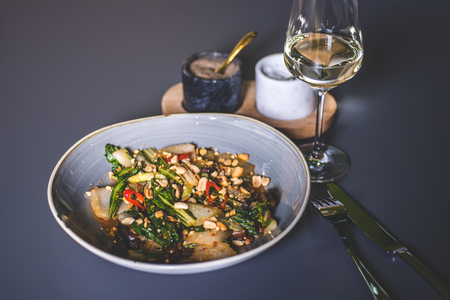 Beautiful view of a dish with peanuts near a glass of white wine. Salad with meat and peanuts with sauce. The knife and fork lie next to the plate. Fougeres with white wine stands on the surface. Marble glasses with spices in the background. Фото со стока