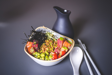 View of the salad with rice and sea cabbage. Square ceramic plate with sea kale and meat. Ceramic rods and a large spoon lie on the surface. A black jar is behind.
