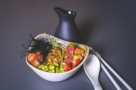 A view of a black jug and a salad of Asian cuisine in a square plate. View of the salad with rice and sea cabbage. Square ceramic plate with sea kale and meat. Ceramic rods and a large spoon lie on the surface. A black jar is behind.
