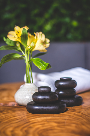 Pyramids of stones for massage lie on the table. White towels lie in the background. Yellow daffodils stand in a white vase.