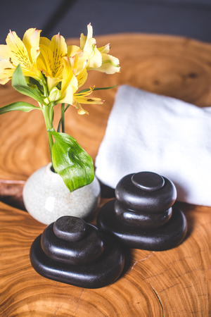 Yellow daffodils and stones for massage lie on a wooden table. View from above. Pyramids of stones for massage lie on the table. White towels lie in the background. Yellow daffodils stand in a white vase.