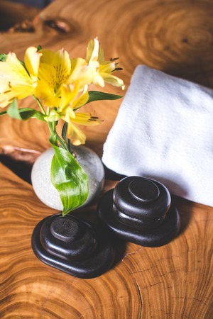 A view from above of yellow flowers in a vase and stones for stone therapy. Yellow daffodils and stones for massage lie on a wooden table. White towels lie in the background. Archivio Fotografico