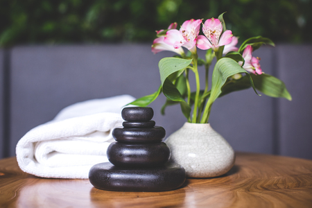 Dark stones for massage are stacked on top of each other on the table. White-pink daffodils stand in a white vase. Pyramids of stones for massage lie on the wooden table. White towels lie in the background. Archivio Fotografico