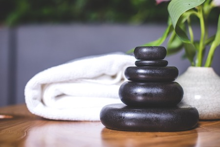 Close-up on dark stones for massage on a wooden table. White towels lie in the background. Archivio Fotografico