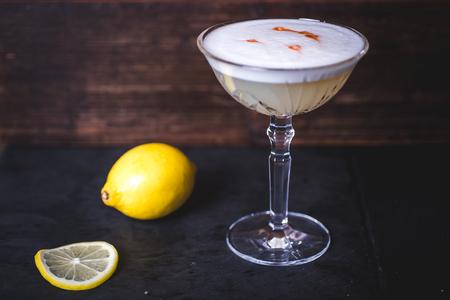Lemon and lemon slice lies near the wine glass.