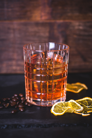A glass with whiskey on a wooden background. Фото со стока
