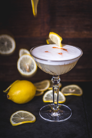 Lemon slices fall into a cocktail.