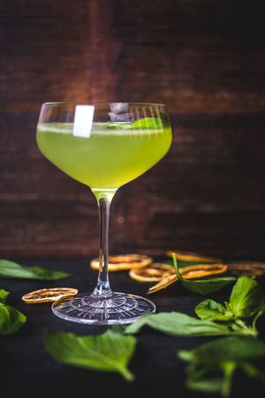 Green cocktail on the background of a wooden background.