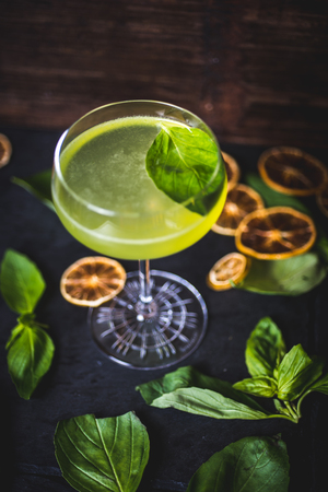 A carbonated cocktail with a mint leaf in a glass.